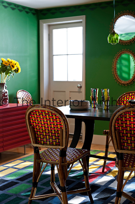 An eclectic dining room with a black wood dining table with french cafe chairs custom colour made by Maison Gatti. The Christopher Farr rug is designed by Sarah Morris whose patterns are based on the reflections of New York sky scrapers. The green walls are in Fennel Green by Sanderson and decorated with stencils by fashion textile designer Sarah Pasricha to compensate for the lack of architectural features in this basement room. The bold colours in this room are complimented with framed posters and lamps by Emery et Cie.