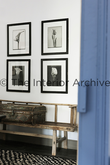 In this corridor four contemporary black-and-white photographic prints hang above a battered but lovingly restored antique bench