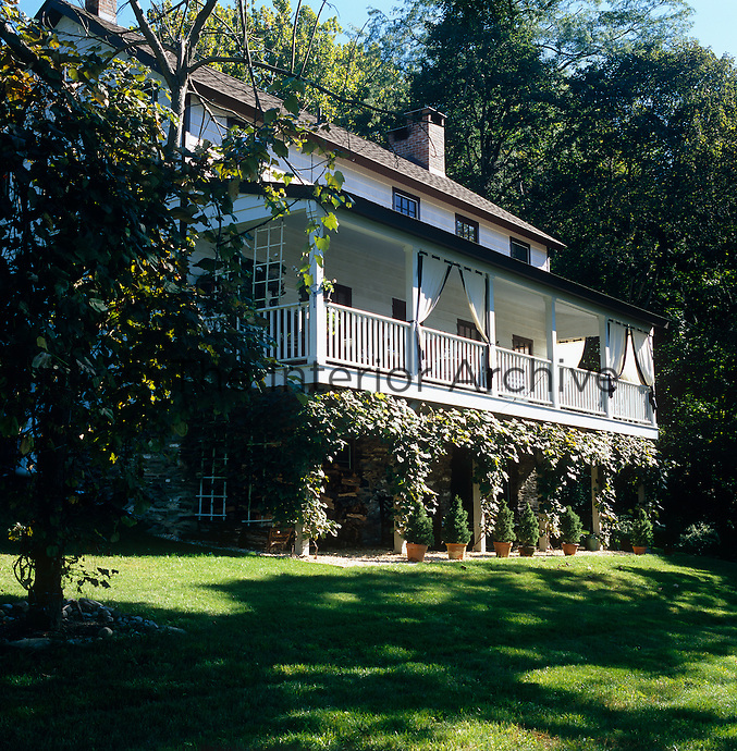Exterior of the clapboard house which was once an Inn with its long veranda overlooking the garden