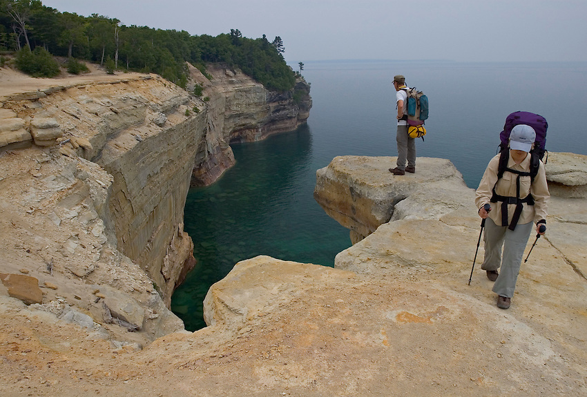 Backpackers hike along cliffs high above Lake Superior in Pictured Rocks National Lakeshore near Munising, Michigan.