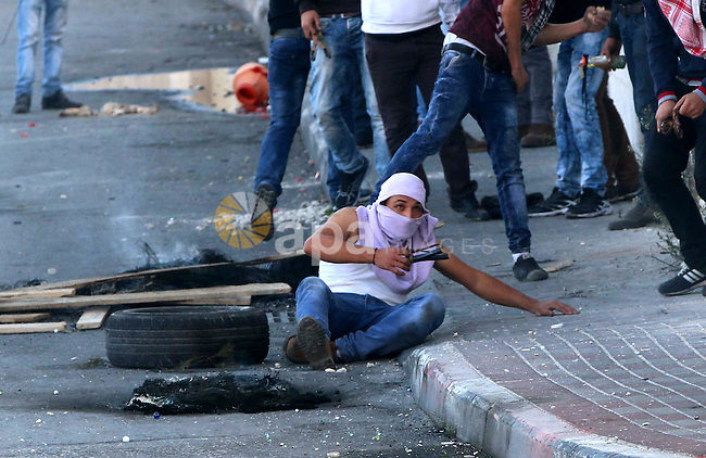 A Palestinian protester uses a sling shot to throw stones towards Israeli security forces during clashes in the West Bank town of Bethlehem on October 9, 2015. Tension and protests rose after an Israeli man on 09 October stabbed four Palestinians in southern Israel, in what is being seen as a revenge attack, officials said. On 08 October several violent incidents happened, including stabbings which left eight Israelis injured, one Palestinian was killed in East Jerusalem and six in the Gaza Strip in clashes with the army while at least six were injured on the West Bank. Photo by Muhesen Amren