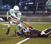 Danville quarterback Jake Madding is pulled down by his jersey by Charleston's Chase Binz in the first half of Friday's football game in Charleston.