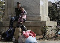 Pictured: A migrant man holds his daughter in Victoria Square, Athens Monday 29 February 2016<br /> Re: Hundreds of migrants have been living in Victoria Square in central Athens Greece