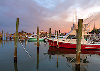 Ocracoke Island, Outer Banks, NC: Colors of sunrise above the boats of Silver Lake Harbor at Ocracoke with Ocracoke Island Lighthouse in the distance