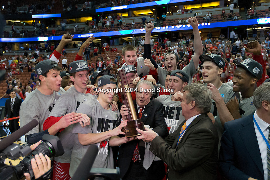 Wisconsin Badgers Head Coach and his team celebrate with the West Regional Trophy after the regional final NCAA college basketball tournament game against the Arizona Wildcats Saturday, March 29, 2014 in Anaheim, California. The Badgers won 64-63 (OT). (Photo by David Stluka)