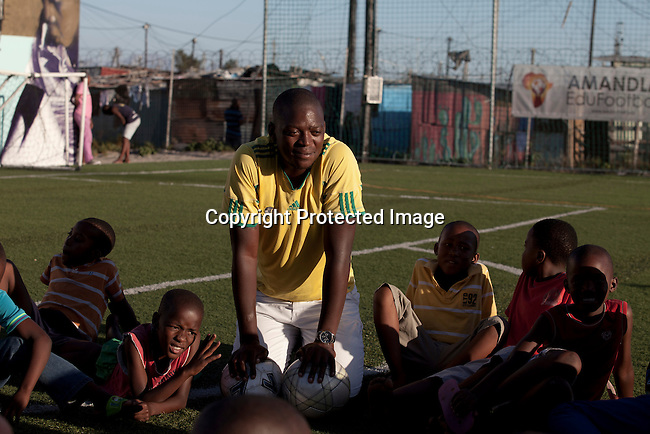 Khayelitsha, South Africa March 11, 2013: Malvin Maras, a Senior leader, holds a skills training session at Amandla EduFootball which was founded by Jakob Schlichti and Florian Zech in the field in Khayelitsha a poor township outside Cape Town, South Africa. They use football to initiate, support educational projects for youth in the township. The program keep children busy and it decreases the risk of them joining gang, criminal activity or teenage pregnancy. The crime level has decreased substantially in the area since the program was created in 2006. (Photo by: Per-Anders Petterssonl)