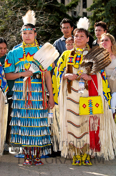 CREE INDIAN WOMEN DRESSED IN TRADITIONAL NATIVE COSTUME AND HOLDING FEATHER FANS IN REGINA, CANADA