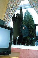Burglar wearing a balaclava and gloves so as he cannot be identified or traced through his fingerprints is climbing through the window of a house. This image may only be used to portray the subject in a positive manner..©shoutpictures.com..john@shoutpictures.com