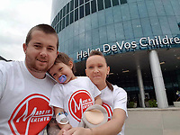 Pictured: Mia Chambers (C) with dad Josh (L) mum Kirsty (R) at the hospital where she received treatment in the USA<br /> Re: A caring schoolgirl who beat cancer has helped save another child with the disease who was let down by the NHS.<br /> Libby Jones, 13, stepped in when funding wasn't available to send five-year-old Mia Chambers for pioneering treatment in America.<br /> Caring Libby asked her classmates to wear all the colours of the rainbow and donate &pound;1.<br /> She came up with &quot;Rainbow Day for Mia&quot; which spread to shops, pubs, clubs, and businesses for miles around.<br /> An incredible &pound;280,000 was raised and Mia was yesterday in Michegan getting the treatment which could save her life.<br /> Libby, who had eye cancer, said: &quot;I was lucky - the NHS paid for me to go to America.<br /> &quot;But it was different for Mia and her parents couldn't afford to take her there.<br /> &quot;So I had a brainwave to ask children in my school to wear all the colours of the Rainbow.&quot;<br /> With help from mum Lindsey the idea was taken up by 27 schools in Merthyr Tydfil, South Wales, where Libby and Mia live.