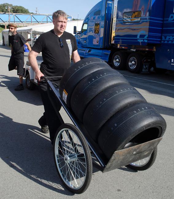 Monterey California, May 4, 2014, Laguna Seca Monterey Grand Prix, Crew member wheels tires through paddock.