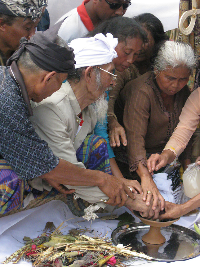 family members join the priest in processing the ashes of the passed family member in an ritual act, cremation ceremonies in Tampak Siring, village of horn carving art, central Bali, archipelago Indonesia, August 2009