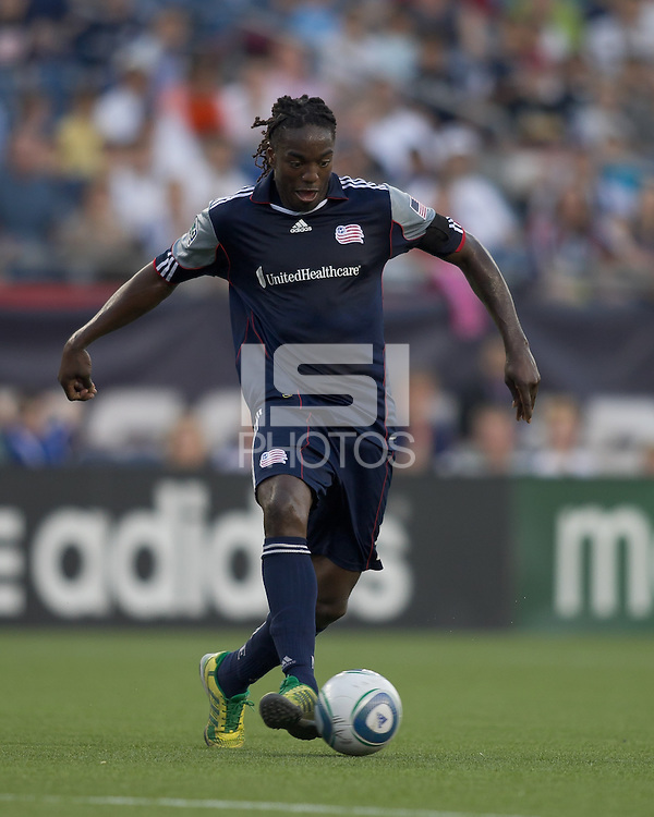 New England Revolution midfielder Shalrie Joseph (21) brings the ball forward. In a Major League Soccer (MLS) match, the New England Revolution tied the Chicago Fire, 1-1, at Gillette Stadium on June 18, 2011.