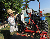 NWA Democrat-Gazette/ANDY SHUPE<br /> Adrian Leffingwell, assistant farm director for The Cobblestone Project Farm in Fayetteville, installs a spool of irrigation tape Tuesday, Sept. 8, 2015, onto a tractor implement while working to prepare for planting. The second Harvest Party, which features information about hunger as well as live music and food, is planned for 6:30 p.m. Sept. 18 at the farm.