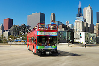 Chicago Double Decker Bus Company's bus carrying tourist on a sightseeing tour through Chicago with teh Sears tower in the background.