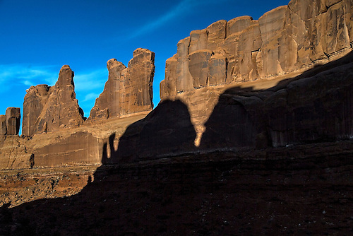 Shadows and silhouettes appear along the sandstone walls at Park Avenue at Arches National Park, Utah