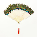 Bris&eacute; Fan, late 19th&ndash;early 20th century; carved and pierced ivory sticks, peacock and peahen feathers, gilt metal bail, silk tassel; H x W (open, with tassel): 53.3 &times; 54.6 cm (21 &times; 21 1/2 in.); Gift of Mrs. James M. Breed; 1964-18-1; Cooper Hewitt, Smithsonian Design Museum. <br />
