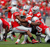 A herd of Buckeye defenders, including defensive end Jamal Marcus (34), linebacker Trey Johnson (36), defensive back Ron Tanner (20) and safety Devan Bogard (30) tackle Florida A&M Rattlers running back Omari Albert (32) during the third quarter of the NCAA football game at Ohio Stadium in Columbus on Sept. 21, 2013. (Adam Cairns / The Columbus Dispatch)