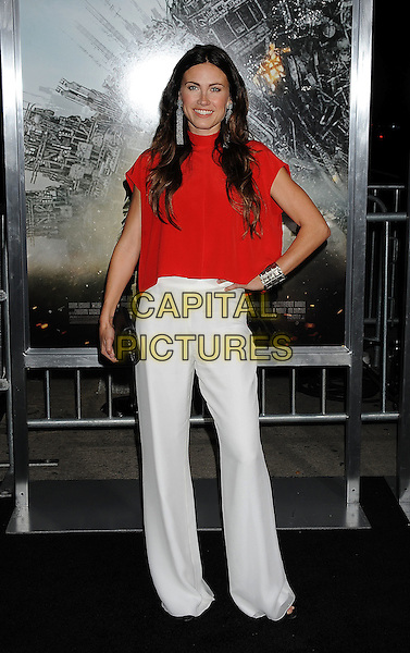 """VAIL BLOOM.Angeles premiere of """"Battle: Los Angeles"""" at the  Regency Village Theatre in Westwood, California, USA..March 8th, 2011.full length top hand on hip black clutch bag silver cuff bracelet red silver dangling earrings trousers flared wide leg.CAP/ROT/TM.© TM/Roth/Capital Pictures"""