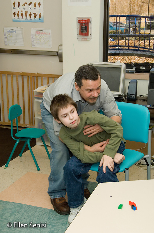 MR / Albany, NY.Langan School at Center for Disability Services .Ungraded private school which serves individuals with multiple disabilities.Teaching assistant gets ready to lift child from his chair. Boy: 10, Duchenne muscular dystrophy, expressive and receptive language delays.MR: Bud2; Sai2.© Ellen B. Senisi