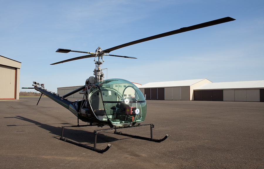 This well-maintained Hiller helicopter sits empty on the airport runway during the daytime.