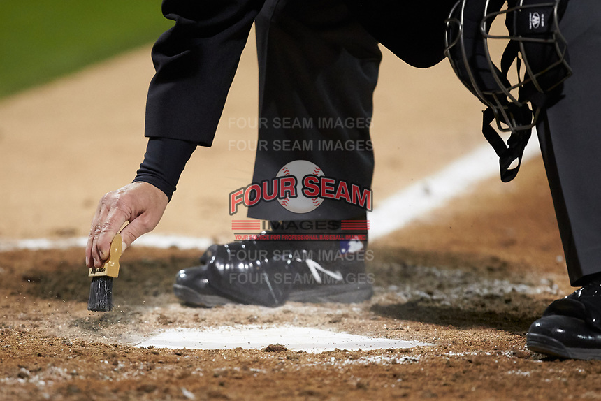 Home plate umpire John Haggerty cleans off home plate during the NCAA baseball game between the Clemson Tigers and the Charlotte 49ers at BB&T BallPark on March 26, 2019 in Charlotte, North Carolina. The Tigers defeated the 49ers 8-5. (Brian Westerholt/Four Seam Images)