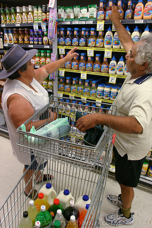 (MODEL RELEASED IMAGE). While the Brown family of Riverview, Australia are used to living with a nearly-empty refrigerator, they look forward to the days when it's full. Every two weeks a new check appears and the family goes to the supermarket. Here, Marge and Doug decide on a salad dressing. (Supporting image from the project Hungry Planet: What the World Eats.)