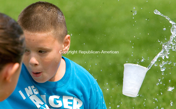 MIDDLEBURY CT. 06 July 2015-070615SV03-Dustin Heege, 9, of Middlebury gets tagged with a cup of water while playing a version of duck duck goose with water at playground camp sponsored by Park and Recreation in Meadowview Park in Middlebury Monday.<br /> Steven Valenti Republican-American