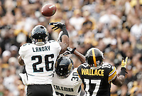 PITTSBURGH, PA - OCTOBER 16:  Dawan Landry #26 and Drew Coleman #30 of the Jacksonville Jaguars defend a pass in front of Mike Wallace #17 of the Pittsburgh Steelers during the game on October 16, 2011 at Heinz Field in Pittsburgh, Pennsylvania.  (Photo by Jared Wickerham/Getty Images)
