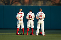 Brett Kinneman (6), Josh McLain (15) and Brock Deatherage (13) of the North Carolina State Wolfpack stand for the National Anthem prior to the game against the Louisville Cardinals at Doak Field at Dail Park on March 24, 2017 in Raleigh, North Carolina. The Wolfpack defeated the Cardinals 3-1. (Brian Westerholt/Four Seam Images)