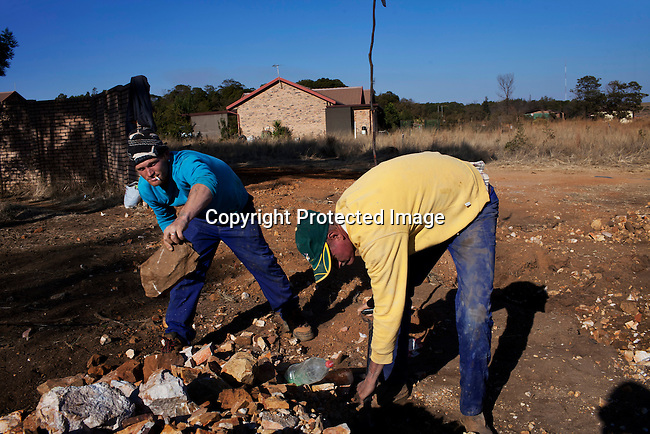 KLEINFONTEIN, SOUTH AFRICA - JULY 15: Municipality workers clean a sewage construction site on July 15, 2013 in Kleinfontein outside Pretoria, South Africa. The all white town with about one thousand residents are all Afrikaners with a Vortrekker heritage. Only white Afrikaners who share Afrikaner culture, language and religion are allowed to settle in the town.  (Photo by: Per-Anders Pettersson)