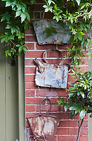Flattened cans and buckets decorate a garden wall next to a garden gate of painted tongue-and-groove
