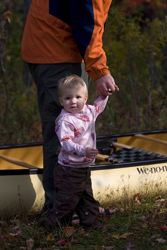 A young girl plays with her dad while canoeing on a fall day near Marquette Michigan.