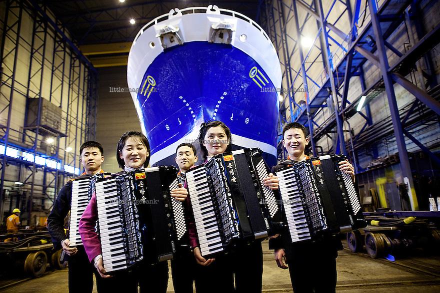 """Kirkenes, Norge, 09.02.2012. """"Take on Me"""" fremføres for de ansatte i skipsverftet Kimek av Kim Chon Ryong (16), Choe Hyang Hwa (16), Kim Ju Yong (15), Han Jin Song (16) og Ri se Ok. Den 1. februar 2012 lastet kunstner Morten Traavik opp en videosnutt på You Tube av Nord-Koreanske ungdommer som spiller A-Ha hiten """"Take on Me"""" på trekkspill. En uke etter ha over en million mennesker sett videoen. En delegasjon Nord-Koreanere er i Kirkenes i forbindelse med festivalen """"Barents Spetakel"""". Foto: Christopher Olssøn"""