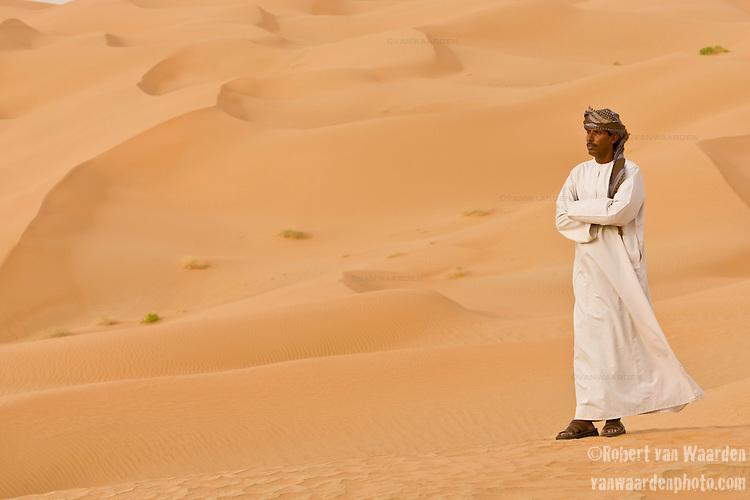 Portrait of an Omani man on sand dunes of the Empty Quarter, Ar Rub Al Khali, Oman.