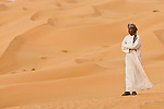 Portrait of an Omani man on sand dunes of the Empty Quarter, Ar Rub Al Khali, Oman.