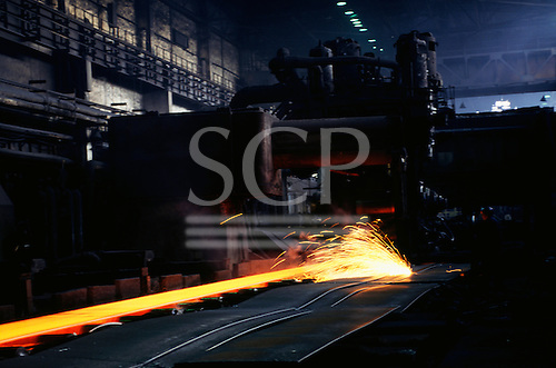 Sofia, Bulgaria. Red-hot sheets of steel and a man cutting another sheet with sparks flying; steelworks.