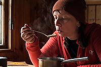 Female hiker enjoys hot meal after long day of hiking at Sälka hut, Kungsleden trail, Lapland, Sweden