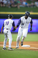 Keon Barnum (20) of the Winston-Salem Dash slaps hands with third base coach Tim Esmay (10) as he rounds the bases after hitting a solo home run in the bottom of the fifth innings against the Wilmington Blue Rocks at BB&T Ballpark on July 30, 2015 in Winston-Salem, North Carolina.  The Dash defeated the Blue Rocks 7-3.  (Brian Westerholt/Four Seam Images)