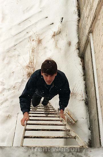 Doug Buzzell climbing a ladder in the snow at an abandoned sugar factory.<br />