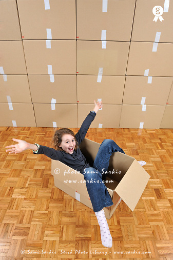 Girl playing inside a cardboard box (Licence this image exclusively with Getty: http://www.gettyimages.com/detail/109862327 )
