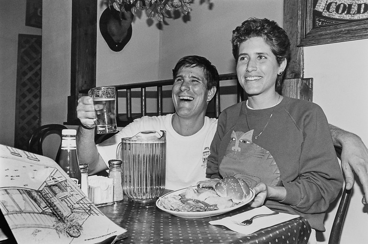 "John McManus and Jeniffer McManus co-owner of ""My Brothers Place"" displays a cheese burger and a pitcher of beer (great beer prices), menu on the left on April 23, 1992. (Photo by Laura Patterson/CQ Roll Call via Getty Images)"