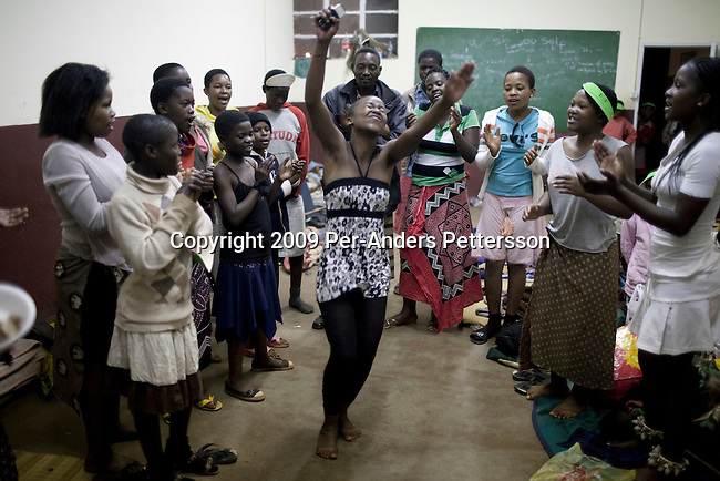 LUDZIDZINI, SWAZILAND - AUGUST 29: Unidentified girls practice their dances in a class room before a traditional Reed dance ceremony at the Royal Palace on August 29, 2009, in Ludzidzini, Swaziland. About 80.000 virgins from all over the country attended this yearly event, which goes on for a week and which is the biggest in Swazi culture. Many of the girls stayed in tents and slept on the ground. It was founded to celebrate the beauty of Swazi women and girls. King Mswati III, and absolute monarch, was born in 1968 and he has 14 wives and many children. The king danced with his men in front of the 80.000 girls. Many of the girls hope to get noticed by the king and to be chosen as a future wife, a ticket from poverty and into a life of privilege and luxury. The country is one of the poorest in the world and it is struggling with a high prevalence of HIV-Aids and severe poverty. (Photo by: Per-Anders Pettersson)..