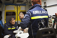 Switzerland. Canton Ticino. Lugano. A man lying down on an emergency medical stretcher is brought at night time by ambulance to hospital for medical examination. The man is suffering from with drug abuse. Team paramedics wear blue uniforms and medical gloves. They all work for the Croce Verde Lugano. The man (L) and the woman (R) are professional certified nurses, the bald man (C) is a volunteer specifically trained in emergency rescue. The patient is connected to a monitor which controls a set of vital functions, such as  electrocardiogram, blood pressure's measurement, respiratory rate and pulse oximetry (oxygen saturation). The Croce Verde Lugano is a private organization which ensure health safety by addressing different emergencies services and rescue services. Volunteering is generally considered an altruistic activity where an individual provides services for no financial or social gain to benefit another person, group or organization. Volunteering is also renowned for skill development and is often intended to promote goodness or to improve human quality of life. Switzerland. Canton Ticino. Lugano. A paramedic takes care of an injured child lying down on stretcher during an emergency medical ride by ambulance. The baby boy fell at home, hurt his head and is brought to hospital for a medical examination. The  paramedic is a professional certified nurse, wearing a blue uniform medical gloves. He works for the Croce Verde Lugano. The bearded paramedic smiles, talks to the child and shows him a brown stuffed bear. The Croce Verde Lugano is a private organization which ensure health safety by addressing different emergencies services and rescue services. Medical gloves are made of different polymers including latex, nitrile rubber, polyvinyl chloride and neoprene. 20.01.2018 © 2018 Didier Ruef