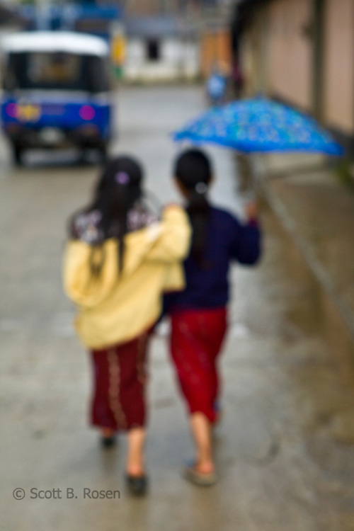 Two young Guatemalan girls walking in rain under umbrella, Nebaj, western highlands, Guatemala