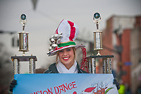 A dance competition winner rides with her trophies in the Westerville Christmas Parade.
