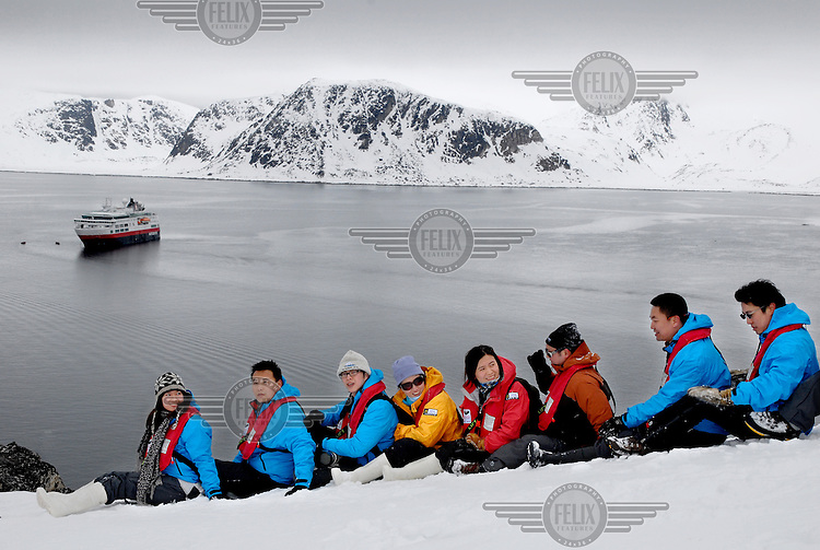 """photograph by XAVIER CERVERA 06/2010.Chinese tourists pose in spontaneous and choral compositions, but very ordered, in Ytre Norskøya Hills, northwestern Spitsbergen island, Svalbard archipielago; on the """"evening landing"""" (usually two per day) from norwegian vessel (made in Italy) MS Fram"""