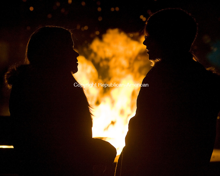 NAUGATUCK, CT - 06 DECEMBER 2009 -120709JT05--<br /> Megan Purcaro, left, 14, talks to her friend Caroline Rentz, also 14, both of Naugatuck, as they keep warm in front of the fire at the Naugatuck Green on Monday during the town's 6th annual Holiday Kickoff, featuring hayrides, Santa Claus, a tree lighting ceremony, a military tree under the gazebo, caroling, and more.<br /> Josalee Thrift Republican-American