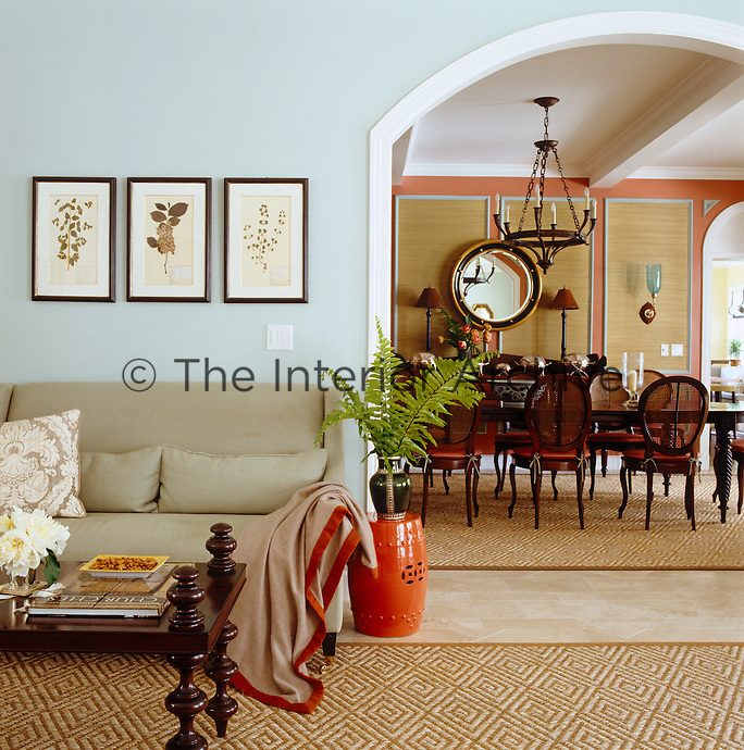 Cool tones of sage green in the living room which adjoins the dining area through an open archway
