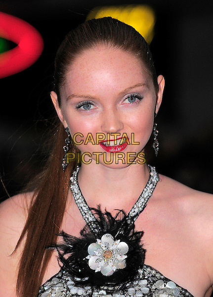 "LILY COLE .Attending the UK film premiere of ""The Imaginarium Of Doctor Parnassus"" at the Empire Leicester Square cinema, London, England, UK, October 6th 2009..portrait headshot red lipstick ponytail hair up white beaded embellished jewel encrusted halterneck straps feathers feather flower corsage black earrings .CAP/BEL.©Tom Belcher/Capital Pictures."