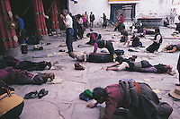 Pilgrims prostrate themselves in front of the Jokhang Temple, Lhasa, Tibet. Some of them will have walked hundreds, if not thousands, of miles to reach this most holy place, prostrating themselves every foot of the way.